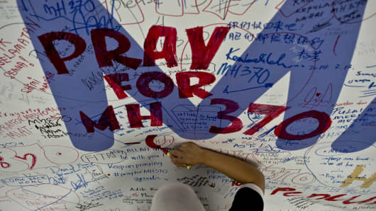 A Malaysia Airlines employee writes a message expressing prayers and well-wishes for passengers onboard missing Malaysia Airlines (MAS) flight MH370 at Kuala Lumpur International Airport in Sepang.